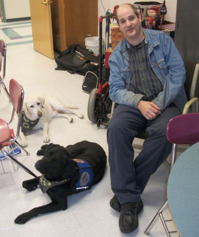 Chris Cotreau with his dogs, Dallas (back left) and Tanner (front left), who were specially trained by Paws with a Cause.