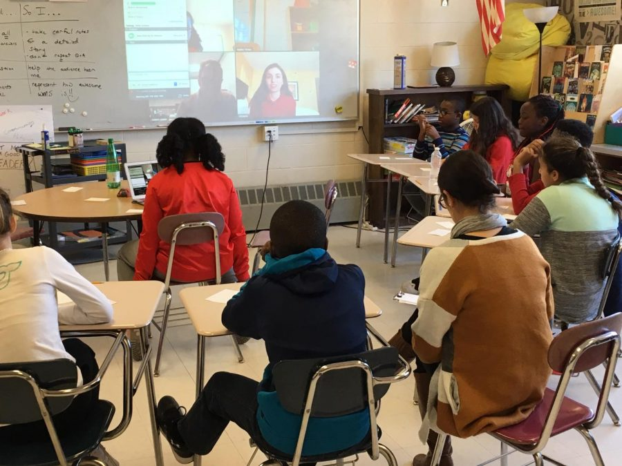 Victoria Newhuis (projected on whiteboard, in red) answers questions from Watertown Middle School students about her upcoming visit to Boston in
