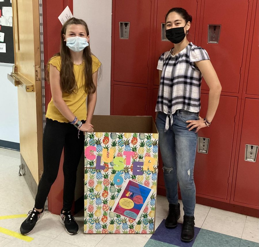 Jojo Jane-Leonardis (left) and Sylvia Sakata stand next one of the collection boxes for the Watertown Middle School clothing drive, which is going on through May 20, 2021.